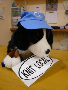 Quincy dog mascot with knit local sticker